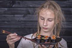 Chica joven del retrato con el sushi, cierre para arriba Fotografía de archivo libre de regalías