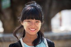 Chica joven del retrato con thanaka en su cara de la sonrisa Mandalay, Myanmar Foto de archivo libre de regalías