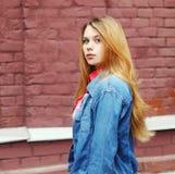 Chica joven del retrato que lleva una chaqueta de los vaqueros en ciudad Fotografía de archivo libre de regalías