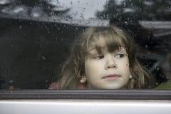 Chica joven del retrato que mira a través de ventana Fotografía de archivo
