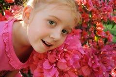 Chica joven delante de las flores rosadas Fotos de archivo