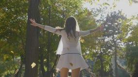Chica joven delgada atractiva que se divierte y que disfruta de la libertad con las hojas de otoño y que hace girar en el parque  almacen de video