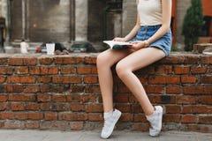 Chica joven delgada que se sienta en una pared de ladrillo y que lee un libro Fotos de archivo