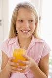 Chica joven dentro que bebe la sonrisa del zumo de naranja Fotografía de archivo