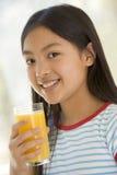 Chica joven dentro que bebe la sonrisa del zumo de naranja Imagenes de archivo
