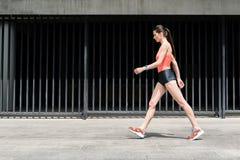 Chica joven deportiva delgada que camina en la calle Fotografía de archivo libre de regalías