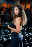 Chica joven deportiva que se resuelve con una pesa de gimnasia imagen de archivo libre de regalías