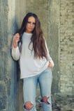 Chica joven deprimida que se coloca al lado de columna concreta en abandone Foto de archivo