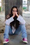 Chica joven deprimida que se sienta en el edificio abandonado Foto de archivo