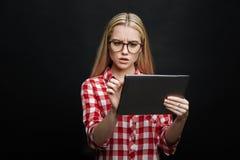 Chica joven desconcertada que usa el dispositivo electrónico en el estudio Fotografía de archivo