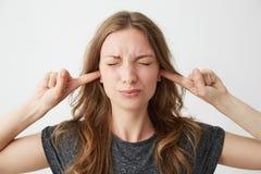 Chica joven descontentada con los ojos cerrados que cierran los oídos que frunce el ceño sobre el fondo blanco Imagenes de archivo
