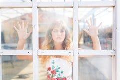 Chica joven detrás de la ventana Imágenes de archivo libres de regalías