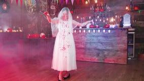 Chica joven disfrazada como novia muerta con su vestido manchado en sangre en un pub adornado Halloween almacen de metraje de vídeo