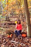 Chica joven divertida con la calabaza y el maíz en otoñal hermoso para Imagen de archivo libre de regalías