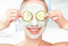 Chica joven divertida con una máscara para la cara y los pepinos de la piel Fotografía de archivo libre de regalías