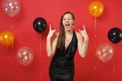 Chica joven divertida en vestido negro que celebra el centelleo, mostrando la muestra del roca-n-rollo en los balones de aire roj foto de archivo