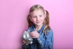 Chica joven divertida enojada con la hucha de plata en fondo rosado Excepto concepto del dinero imagenes de archivo