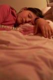 Chica joven dormida en cama en la noche Imagenes de archivo