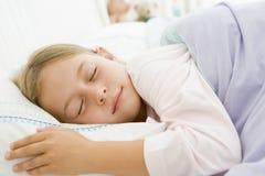 Chica joven dormida en su cama Imagen de archivo libre de regalías