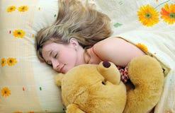 Chica joven dormida en su cama con un oso de peluche Imagen de archivo