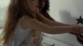 Chica joven dos en casa que juega metrajes