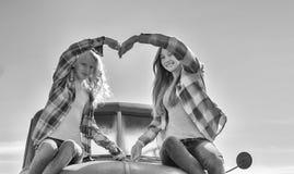 Chica joven dos que hace los brazos del corazón Imagen de archivo