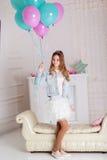 Chica joven dulce con los globos azules y rosados Imagenes de archivo