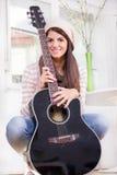 Chica joven dulce que sostiene la guitarra Fotografía de archivo libre de regalías