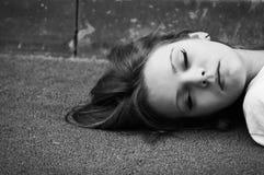 Chica joven durmiente que miente en el asfalto Fotografía de archivo