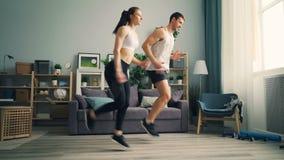Chica joven e individuo en la ropa de deportes que corre en casa hacer deportes junto que entrenan almacen de metraje de vídeo