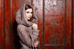 Chica joven elegante de moda en chaqueta con la capilla que se coloca cerca foto de archivo