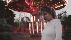 Chica joven elegante en los vidrios que colocan la atracción cercana del carrusel en parque del amusment metrajes