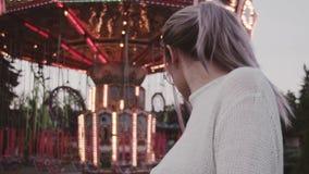 Chica joven elegante en los vidrios que presentan cerca de la atracción del carrusel en parque del amusment almacen de video