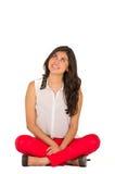 Chica joven elegante hermosa que se sienta sobre blanco Foto de archivo