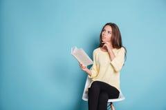 Chica joven elegante pensativa que piensa en algo sobre fondo azul Imagenes de archivo