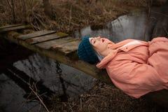 Chica joven elegante que descansa sobre la orilla del río, mintiendo en un pequeño puente de madera imagen de archivo libre de regalías