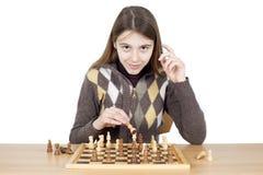 Chica joven elegante que juega a ajedrez - el buen juego de ajedrez requiere inteligencia, paciencia y buena estrategia Foto de archivo