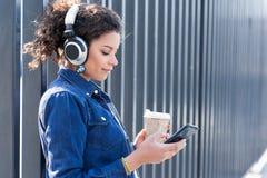 Chica joven elegante que se coloca con el auricular y el café express en calle Imagen de archivo libre de regalías