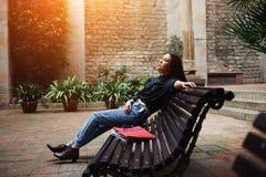 Chica joven elegante que se sienta en el banco Fotografía de archivo