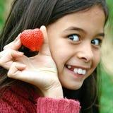 Chica joven emocionada que muestra la fresa roja jugosa. fotografía de archivo