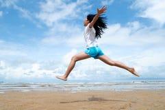 Chica joven emocionada que salta en el aire Fotografía de archivo