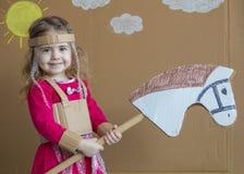 Chica joven en caballo de palillo handmade fondo del sol pintado y de las nubes blancas fotos de archivo libres de regalías