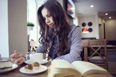 Chica joven en café con el libro Imagenes de archivo