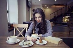 Chica joven en café con el libro Fotografía de archivo