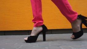 Chica joven en caminar negro de los tacones altos abajo de la calle almacen de metraje de vídeo