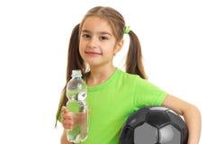 Chica joven en camisa verde con la bola en manos Imagen de archivo libre de regalías