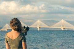 Chica joven en camiseta con el trípode y cámara que toma la imagen del puente de Rion-Antirion Patras Grecia Fotografía de archivo libre de regalías