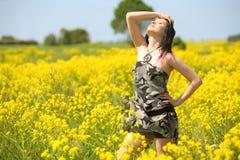 Chica joven en campo de flor amarillo Fotos de archivo