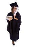 Chica joven en capa del estudiante con el diploma y la pila de libros Fotos de archivo