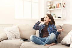 Chica joven en casa que habla en el teléfono móvil Fotografía de archivo libre de regalías